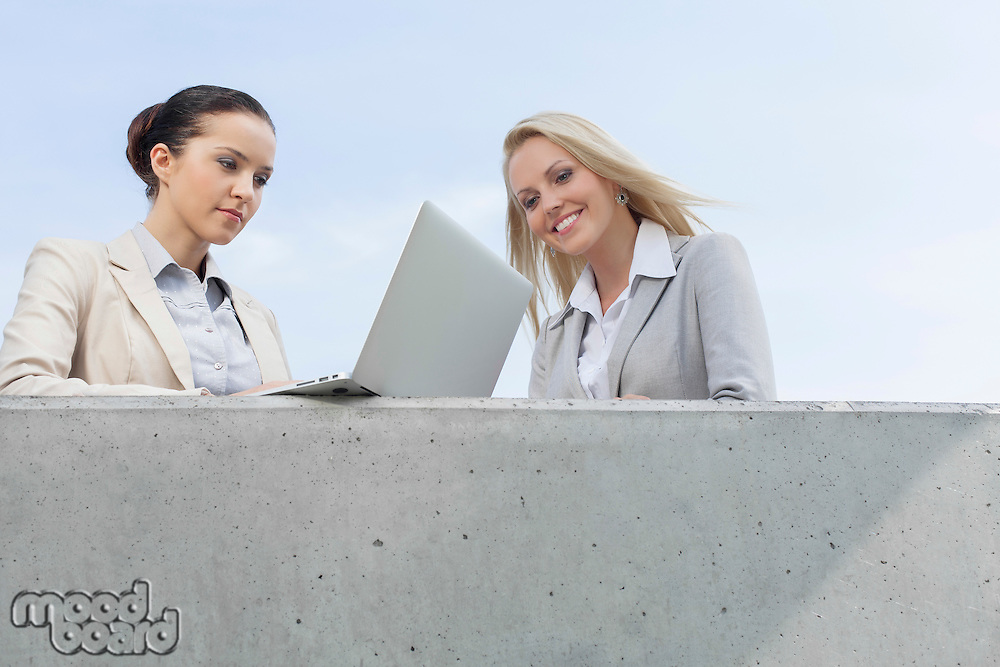 Low angle view of businesswoman using laptop while standing with colleague on terrace against sky