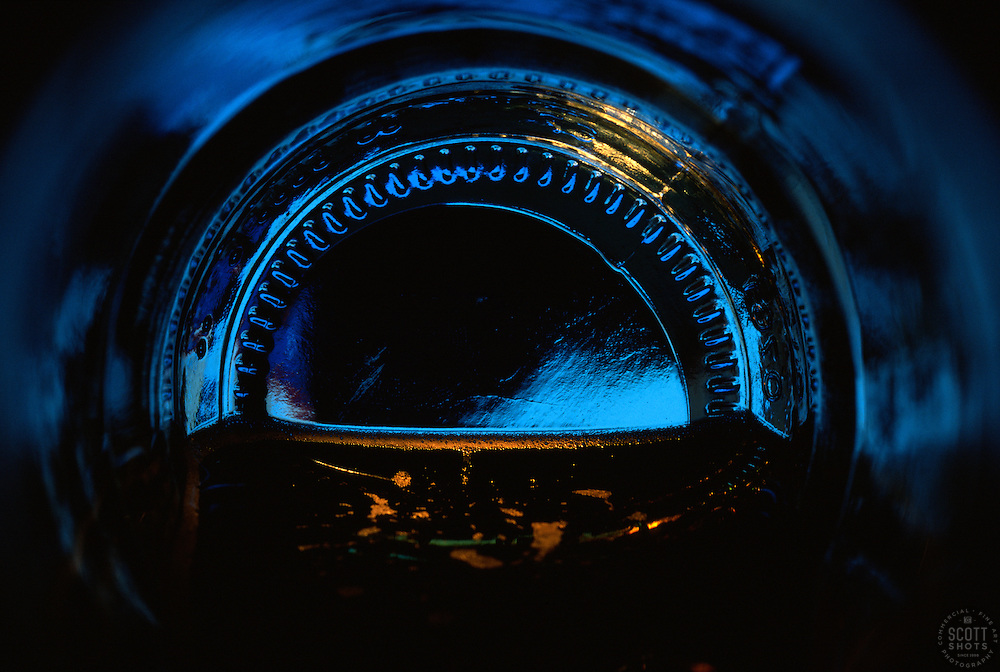 """Beauty at the Bottom: Moonlight""- This image is a photograph of a beer bottle shot right down the mouth of the bottle. A television provides the main light source."