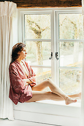 Woman Sitting on Window Sill Looking out