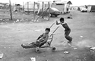 Rome June 1999.Children playing with a pram, rom Romanian, in the Rom's camp  Casilino 700.