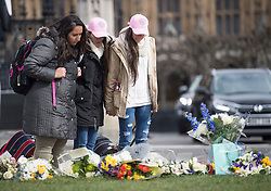 © Licensed to London News Pictures. 22/03/2018. London, UK. Emotional members of the public look at flowers left on Parliament Square, outside the Houses of Parliament in Westminster, London on the one year anniversary of the the Westminster Bridge Terror attack. A lone terrorist killed 5 people and injured several more, in an attack using a car and a knife. The attacker, 52-year-old Briton Khalid Masood, managed to gain entry to the grounds of the Houses of Parliament and killed police officer Keith Palmer. Photo credit: Ben Cawthra/LNP