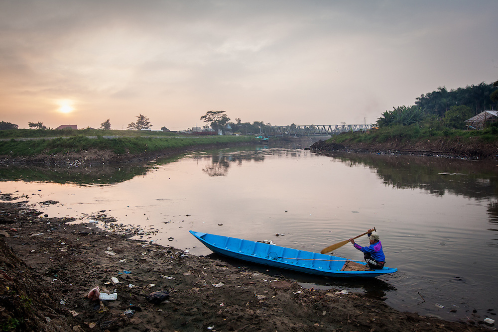 Abah Dayat looks for scraps on the Citarum River.  He used to be a fisherman but couldn't earn enough money to support his family due to the significant decline in the number of fish in the river. Citeureup Village, Kabupaten Bandung...Credit: Andri Tambunan for Greenpeace