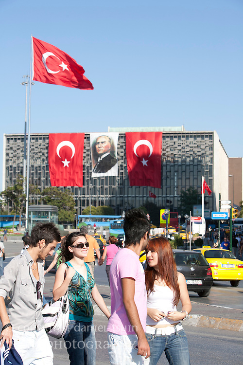 Pedestrians walking in Taksim Square with Turkish flags unfurled behind them, close to Victory Day in late August.