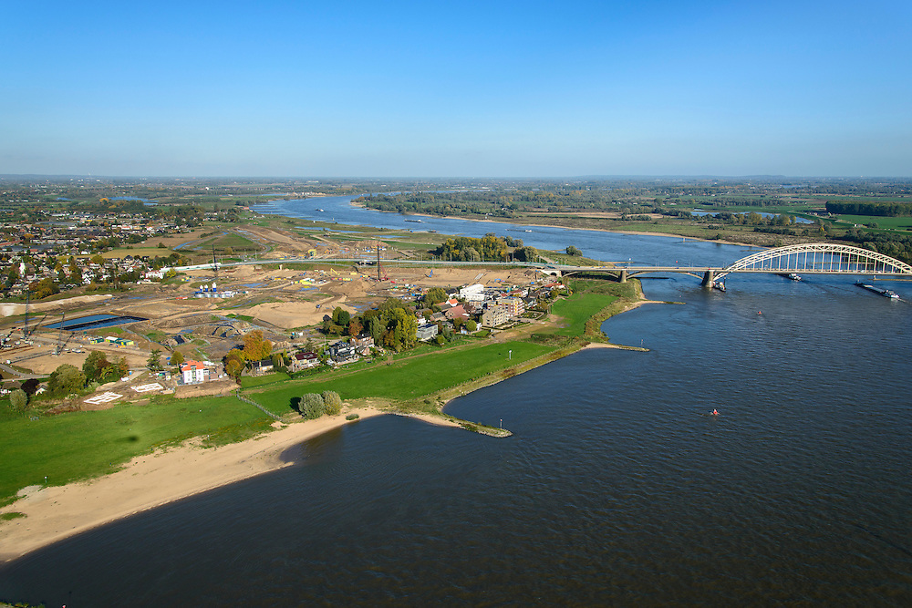 Nederland, Gelderland, Nijmegen, 24-10-2013; rivier de Waal met Waalbrug, daarvoor de toerit naar / en de spoorbrug met fietspad De Snelbinder gezien vanuit het Westen. Rechts de binnenstad van Nijmegen. Links van de rivier grondwerkzaamheden voor de dijkteruglegging Lent (Ruimte voor de Rivier) .  De dijken worden landinwaarts verplaats en er wordt een nevengeul gegraven. In de verte de Waalbrug, de bebouwing voor de brug blijft bestaan en komt te liggen op het Stadseiland Veur-Lent Nijmegen.<br /> The river Waal and first the railway bridge with cycle path De Snelbinder (The Luggage strap) and next the Waal bridge. View on inner city of Nijmegen. The river groundwork for the Dike relocation of Lent (project Ruimte voor de Rivier: Room for the River). <br /> luchtfoto (toeslag op standaard tarieven);<br /> aerial photo (additional fee required);<br /> copyright foto/photo Siebe Swart.