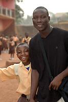 Ghana, Accra, Kokomlemle, 2007. An older brother arrives together with a pupil at Kwameh Nkrumah Memorial School.