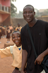Ghana, Accra, Kokomlemle, 2007. An older brother arrives together with a pupil at Kwameh Nkrumah Memorial School.