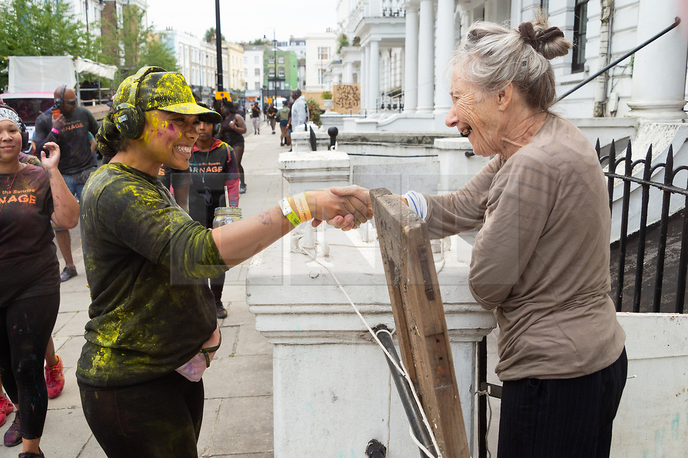© Licensed to London News Pictures. 26/08/2018. London, UK. A reveller shakes hand with a local resident during Jouvert, a paint fight that officially marks the start of the Notting Hill carnival. The two day event is the second largest street festival in the world after the Rio Carnival in Brazil, attracting over 1 million people to the streets of West London. Photo credit: Ray Tang/LNP