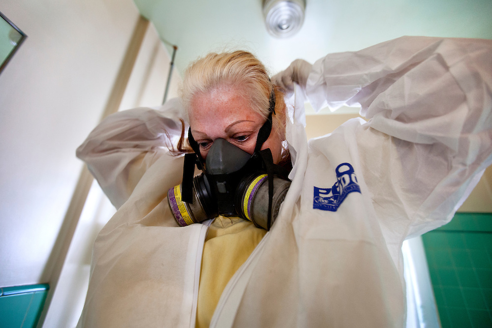 Kathie Jo Kadziauskas puts on her respirator in preparation to chemically fog a house in which a man had passed away in Los Angeles, Calif. on Tuesday, March 13, 2012. (photo by Gabriel Romero ©2012)