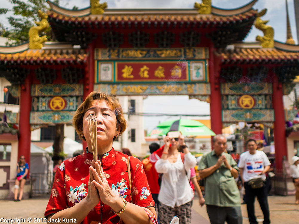 "19 FEBRUARY 2015 - BANGKOK, THAILAND: A woman prays at the entrance to the Thian Fah Shrine in Bangkok's Chinatown. 2015 is the Year of Goat in the Chinese zodiac. The Goat is the eighth sign in Chinese astrology and ""8"" is considered to be a lucky number. It symbolizes wisdom, fortune and prosperity. Ethnic Chinese make up nearly 15% of the Thai population. Chinese New Year (also called Tet or Lunar New Year) is widely celebrated in Thailand, especially in urban areas that have large Chinese populations.    PHOTO BY JACK KURTZ"