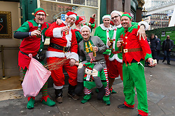 © Licensed to London News Pictures. 22/12/2017. London, UK. Office workers dressed as elves drink beer outside the Railway Tavern pub in Liverpool Street in the City of London. Many office workers in the City appear to have finished work early today and have headed to pubs and bars or started their Christmas getaway early on Frantic Friday. Photo credit: Vickie Flores/LNP