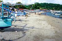 Bali, Karangasem, Padangbai. Fishing boats and children playing in the sand.
