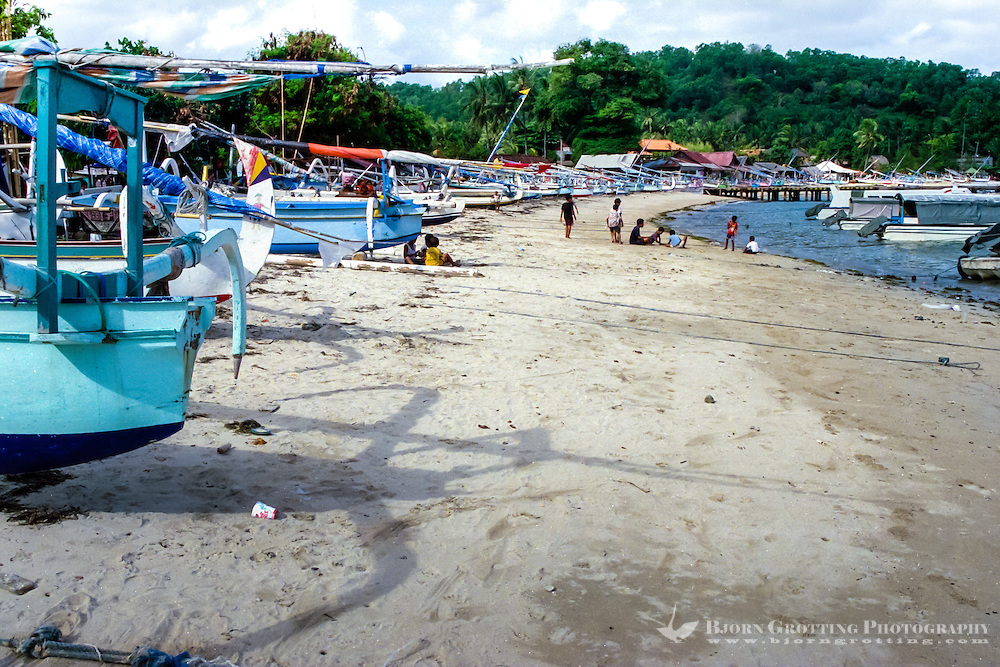 Bali, Karangasem, Padangbai. Fishing boats and children playing in the sand.