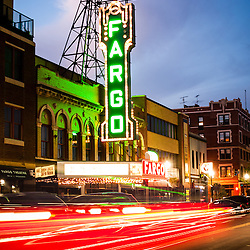 Photo of Fargo Theater and downtown Fargo buildings at night with motion blurred car lights along North Broadway Drive. The Fargo Theatre was built in 1926 and is on the National Register of Historic Places. The Fargo Theatre is currently a popular venue for films, movies, concerts, plays and other live events. Photo is vertical and was taken in 2011.