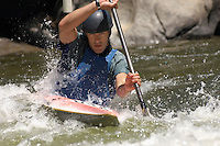Young man whitewater kayaking