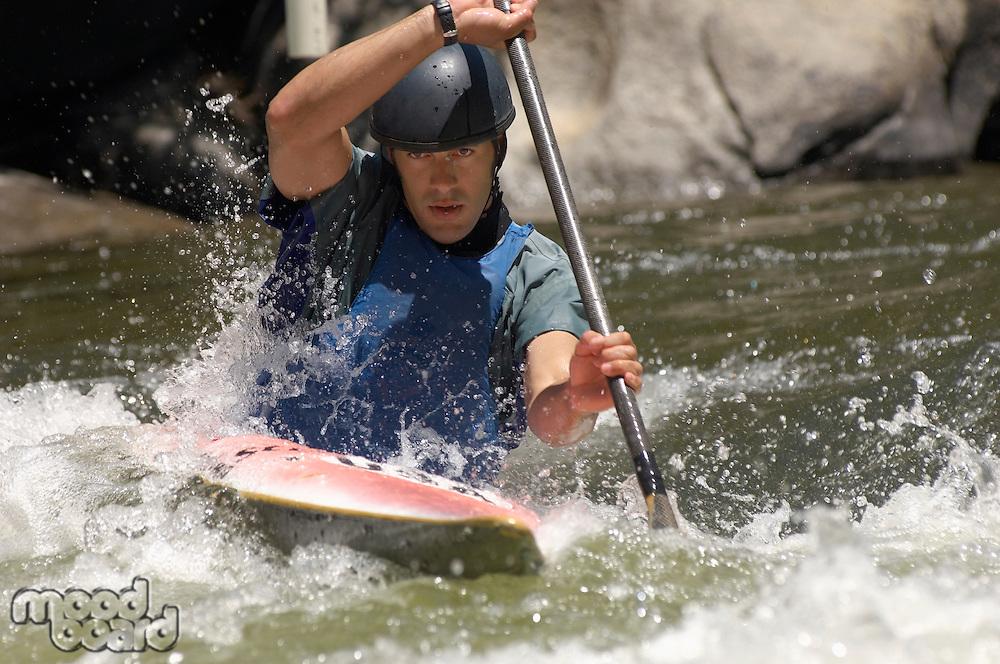Young man whitewater kayaking