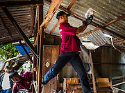 03 SEPTEMBER 2016 - BANGKOK, THAILAND: Bangkok city workers tear down one of the 12 homes scheduled for demolition in the Pom Mahakan community. Hundreds of people from the Pom Mahakan community and other communities in Bangkok barricaded themselves in the Pom Mahakan Fort to prevent Bangkok officials from tearing down the homes in the community Saturday. The city had issued eviction notices and said they would reclaim the land in the historic fort from the community. People prevented the city workers from getting into the fort. After negotiations with community leaders, Bangkok officials were allowed to tear down 12 homes that had either been abandoned or whose owners had agreed to move. The remaining 44 families who live in the fort have vowed to stay.      PHOTO BY JACK KURTZ