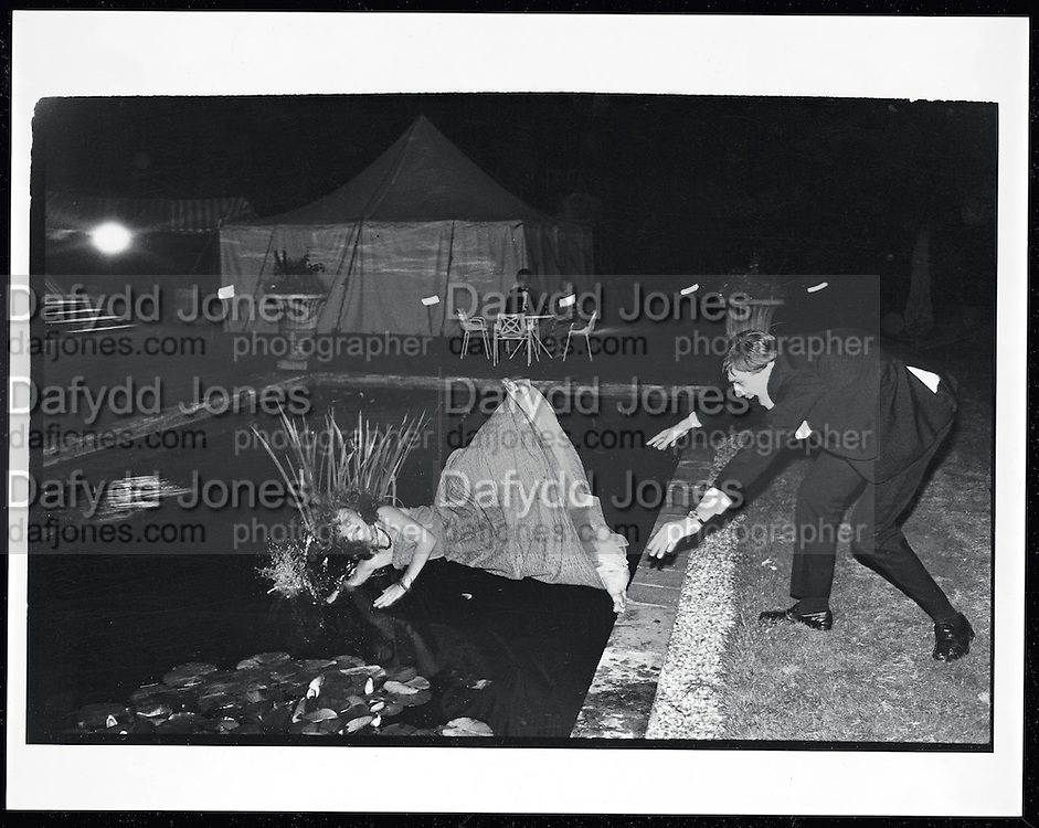 Film 82660f12 Debutante in a Lily pond. Pop Vincent pushed in by Charles Mcdowel during the Martin Betts Dance. Ascot. 23 July 1982. Not a good idea to have a party  near a pond.   During the evening several guests ended up in the pond including the girl that gave the party! ( I missed that picture )  I 'd drunk a glass of wine which may have slowed my reactions down to that last possible moment. The reeds add to the drama looking like an exaggerated splash.