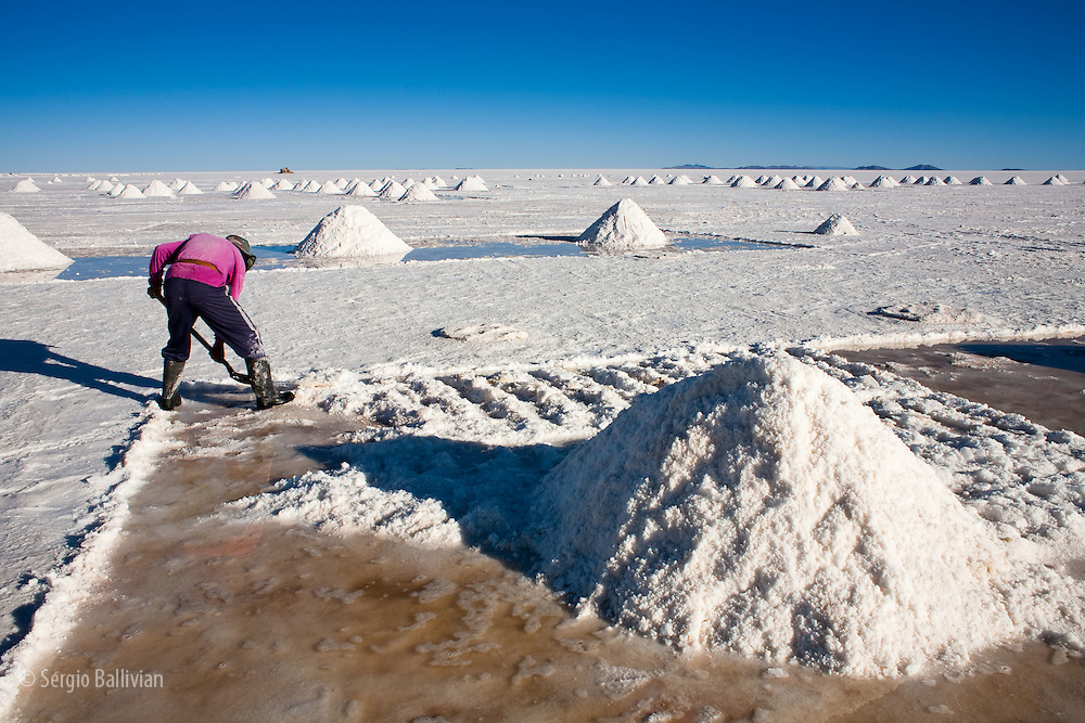 The mining of salt by hand is practiced by locals in the Salar de Uyuni, Bolivia.  By using picks and shovels the salt is piled high into pyramids to drain the water.  Once dry it is shoveled into open bed trucks that take it a few kilometers to Colchani for further processing by hand and using antiquated machinery.