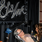 Els Ink tattoo a client at The Great British Tattoo Show, on 26 May 2019, London, UK.