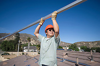 A man lifting a large metal pole on a roof top