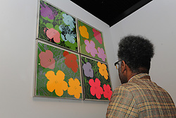 © Licensed to London News Pictures. 21/10/2013. London, UK. A man views Flowers by Andy Warhol at The Pop Art Design Exhibition at The Barbican Centre preview. Photo credit : David Mirzoeff/LNP