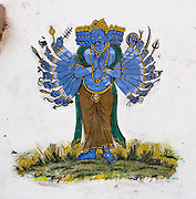 A Hindu artwork of a diety with many arms, faces, and weapons is portrayed on a wall in Kathmandu, Nepal, Asia.