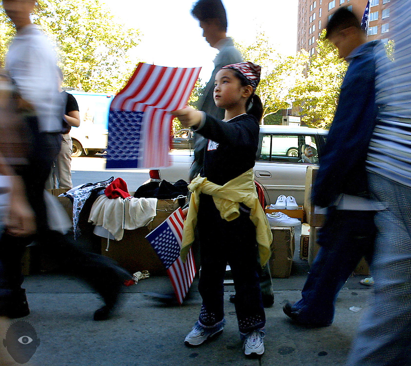 A young Chinatown resident sells American flags which helps to contribute cash to aid families of the disaster victims. It was an area dominated by the visage of the World Trade Center and the residents there feel the great loss.
