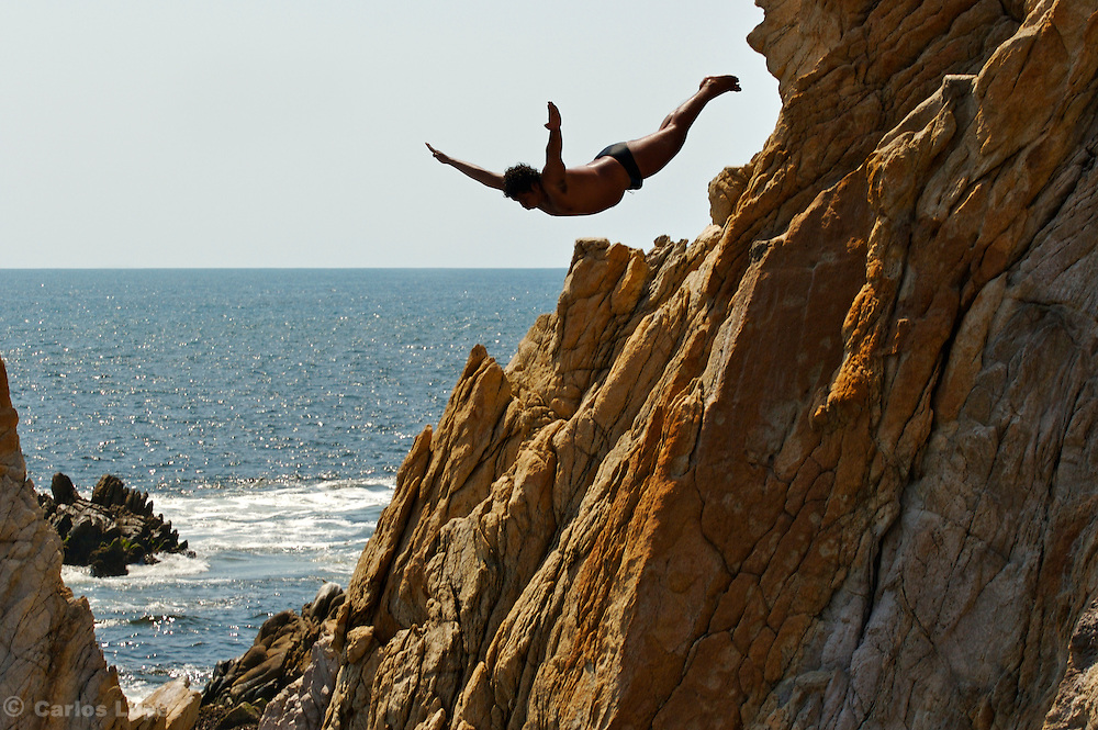 A CLIFF DIVER IS JUMPING FROM  A ROCK CALLED LA QUEBRADA IN ACAPULCO AS PART OF THE TOURISTIC SHOW OF EVERY DAY.