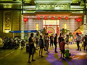 "13 FEBRUARY 2019 - SIHANOUKVILLE, CAMBODIA: People gather in front of the New MGM Casino, a Chinese owned casino in Sihanoukville. There are about 80 Chinese casinos and resort hotels open in Sihanoukville and dozens more under construction. The casinos are changing the city, once a sleepy port on Southeast Asia's ""backpacker trail"" into a booming city. The change is coming with a cost though. Many Cambodian residents of Sihanoukville  have lost their homes to make way for the casinos and the jobs are going to Chinese workers, brought in to build casinos and work in the casinos.      PHOTO BY JACK KURTZ"