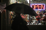 Pine Bush, NY - People use an umbrella to stay dry in front of a store as snow falls during the Pine Bush Festival of Lights on Dec. 5, 2009.