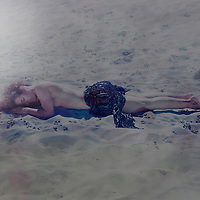 Portrait of a young woman with tanned skin and blonde hair lying on hot sand in the summer