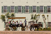 Horse carriage passing a home on Rainbow Row in historic Charleston, SC.