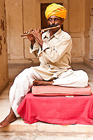 Portrait of seated man wearing a turban playing a flute, India. Exotic people and places wall art. Fine art photography prints for sale.