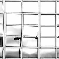 The abstract reflection of street lights in the glass facade of a modern building.