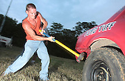David W. Smith/ Daily News<br /> Dewey Jessie from Scottsville pounds the metal on a car back into place before a compact car demolition derby at the SOKY Fair Thursday.