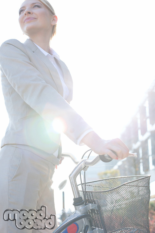Low angle view of businesswoman standing with bicycle on sunny day