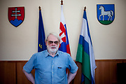 """Mr. Cyril Revak, the mayor of Ostrovany in eastern Slovakia, in front of flags, the Slovak Emblem (left) and the local emblem of Ostrovany (right). Mayor Mr. Rehak sees the wall dividing private properties from the neighbouring Roma settlement as a """"fence"""" and not a wall."""