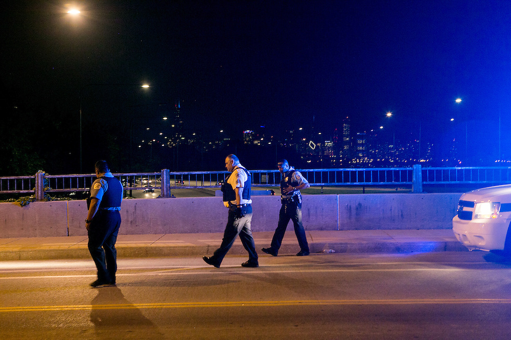 CHICAGO, IL - MAY 29, 2016: Chicago police officers search for bullet casings above Lake Shore Drive at the scene of a shooting near 1058 East Oakwood Boulevard in  Chicago, Illinois. CREDIT: Sam Hodgson for The New York Times.