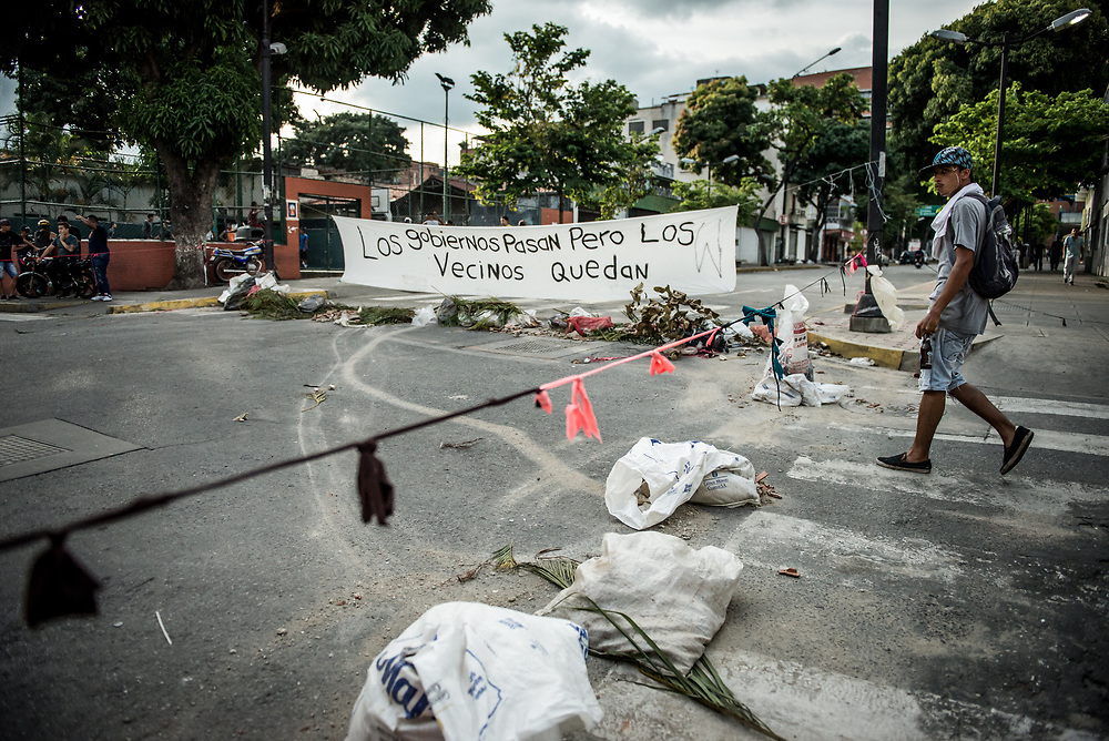 "CARACAS, VENEZUELA - JULY 27, 2017: A road blocked by protesters, with a sign that says, in Spanish: ""Governments pass, but neighbors stay"" built in support of a national strike, called by the political opposition to last for  48 hours, all day July 26th and 27th. They called for their supporters to close businesses, not go to work, and instead create barricades to block off their streets.  Opposition controlled areas of the country were completely shut down.  The strike was called as part of the opposition's civil resistance movement - that began on April 1st, to protest against the Socialist government's attempt to elect a new constituent assembly that will have the power to re-write the constitution, and will threaten democracy.  PHOTO: Meridith Kohut for The New York Times"