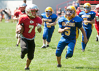 Jacob Marovich carries the ball down field past Thomas Pellerin during the Laconia Chiefs U5 division matchup with the Franklin Tilton Falcons at the Laconia Youth Football Jamboree Saturday. (Karen Bobotas/for the Laconia Daily Sun)Laconia Youth Football Jamboree Saturday,  August 20, 2011.