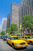 Traffic with yellow taxi cabs on Park Avenue with office skyscrapers of Midtown Manhattan, New York City.