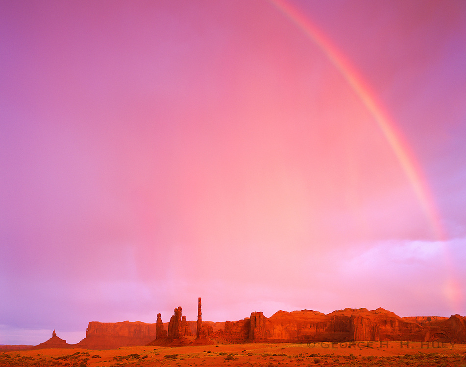 0195-1059LVT ~ Copyright: George H. H. Huey ~ Rainbow over the Totem Pole and Yei Bi Chai Rocks. Monument Valley, Arizona.