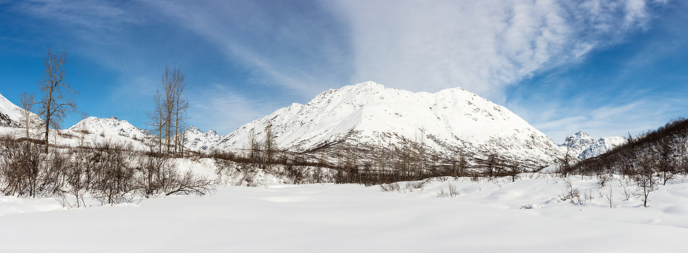 Deep snow covers the Little Susitna River with Idaho Peak and the Talkeetna Mountains in the background in Hatcher Pass in Southcentral Alaska. Afternoon. Winter.