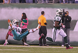 October 17, 2011; East Rutherford, NJ, USA; New York Jets running back Joe McKnight (25) breaks a tackle by Miami Dolphins wide receiver Roberto Wallace (18) during the first half at the New Meadowlands Stadium.