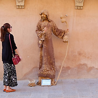 ASSISI, ITALY - OCTOBER 03:  A tourist admires an actor impersonating Saint Francis on October 3, 2013 in Assisi, Italy. Pope Francis is due to venerate the tomb of San Francesco of Assisi tomorrow during his one-day visit to the city.  (Photo by Marco Secchi/Getty Images)