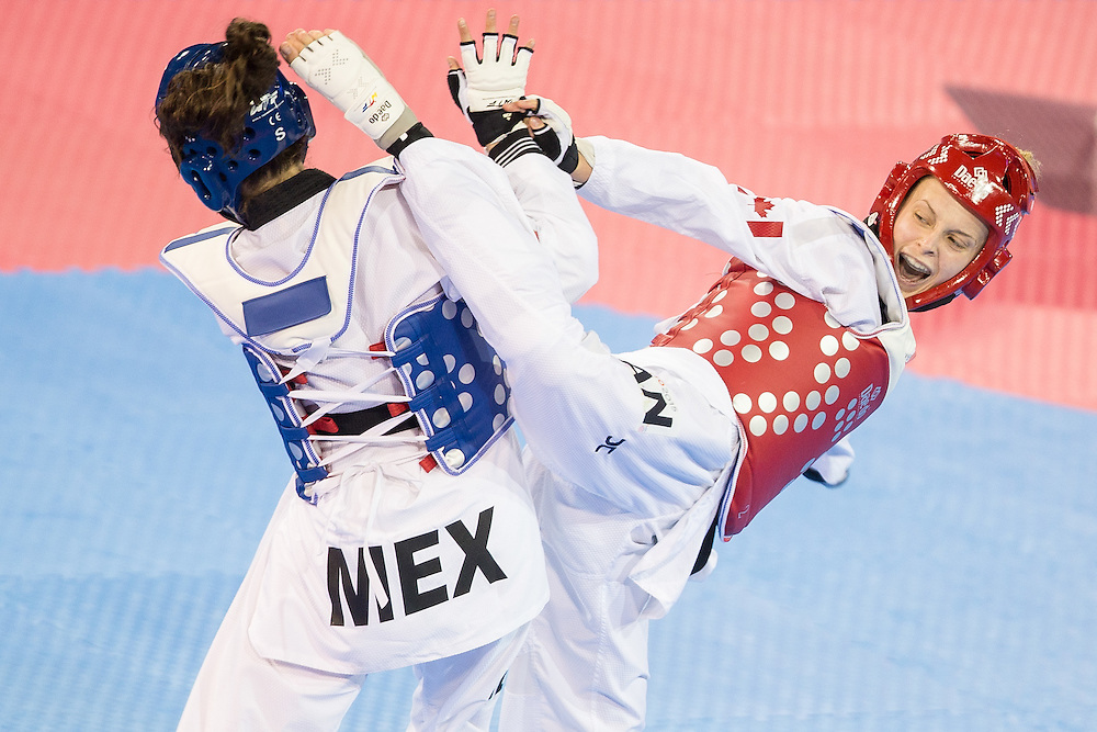 Evelyn Gonda (R) of Canada tries to kick Paulina Armeria of Mexico during their semifinal contest in the women's -57kg weight class of Taekwondo at the 2015 Pan American Games in Toronto, Canada, July 20,  2015.  AFP PHOTO/GEOFF ROBINS