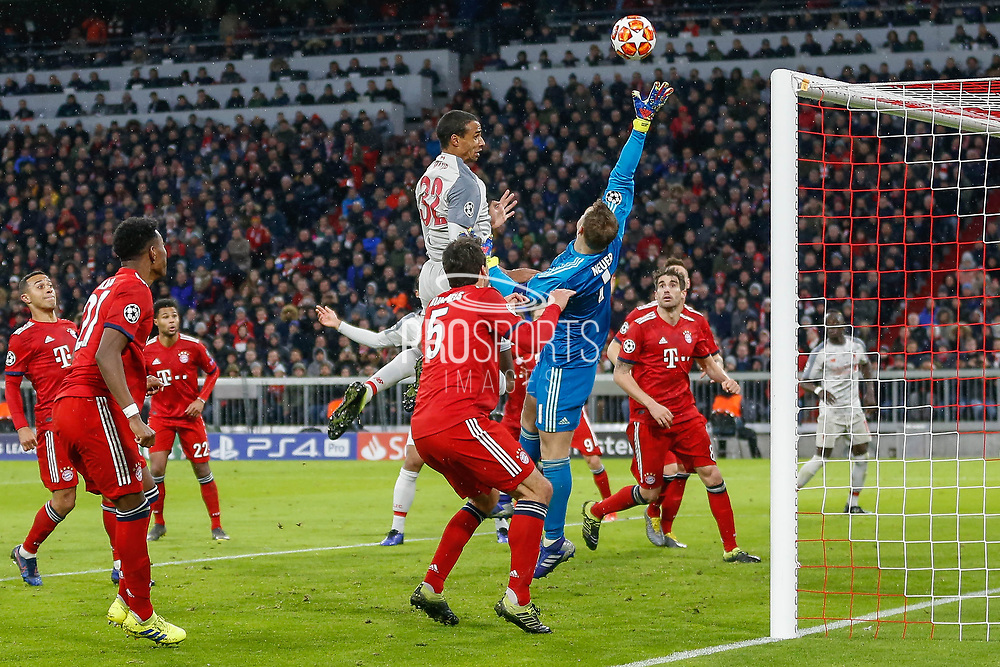 Liverpool defender Joel Matip (32) battles in the air with Bayern Munich goalkeeper Manuel Neuer (1) during the Champions League match between Bayern Munich and Liverpool at the Allianz Arena, Munich, Germany, on 13 March 2019.