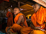 "02 JULY 2013 - ANGKOR WAT, SIEM REAP, SIEM REAP, CAMBODIA:  Buddhist novices at a small monastery near the Bayon temple in the Angkor Wat complex. Angkor Wat is the largest temple complex in the world. The temple was built by the Khmer King Suryavarman II in the early 12th century in Yasodharapura (present-day Angkor), the capital of the Khmer Empire, as his state temple and eventual mausoleum. Angkor Wat was dedicated to Vishnu. It is the best-preserved temple at the site, and has remained a religious centre since its foundation – first Hindu, then Buddhist. The temple is at the top of the high classical style of Khmer architecture. It is a symbol of Cambodia, appearing on the national flag, and it is the country's prime attraction for visitors. The temple is admired for the architecture, the extensive bas-reliefs, and for the numerous devatas adorning its walls. The modern name, Angkor Wat, means ""Temple City"" or ""City of Temples"" in Khmer; Angkor, meaning ""city"" or ""capital city"", is a vernacular form of the word nokor, which comes from the Sanskrit word nagara. Wat is the Khmer word for ""temple grounds"", derived from the Pali word ""vatta."" Prior to this time the temple was known as Preah Pisnulok, after the posthumous title of its founder. It is also the name of complex of temples, which includes Bayon and Preah Khan, in the vicinity. It is by far the most visited tourist attraction in Cambodia. More than half of all tourists to Cambodia visit Angkor.         PHOTO BY JACK KURTZ"