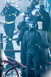 © Licensed to London News Pictures. 14/06/2017. London, UK. Police in riot equipment at the scene of a huge fire at Grenfell tower block in White City, London. The blaze engulfed the 27-storey building with 200 firefighters attending the scene. There were reports of people trapped in the building. Photo credit: Guilhem Baker/LNP