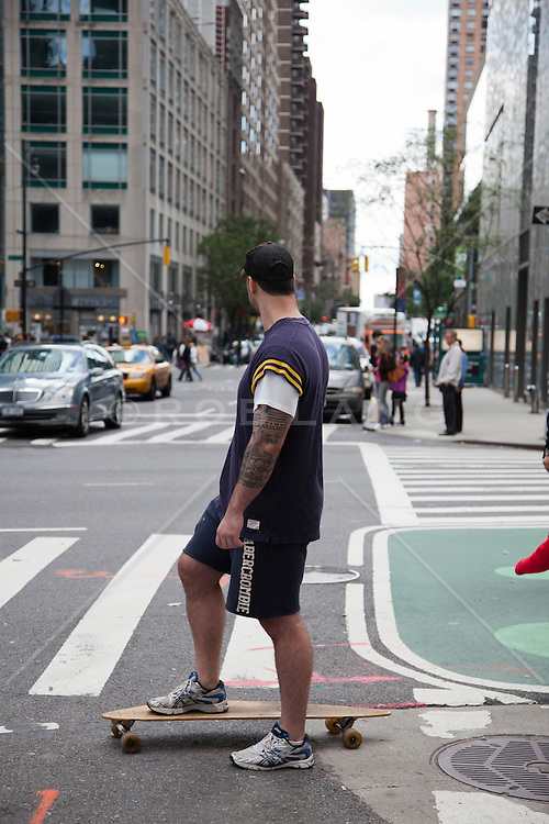 man with tattoos on a skateboard in New York City